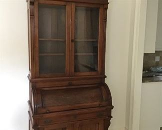 Antique roll top desk with attached bookshelf.