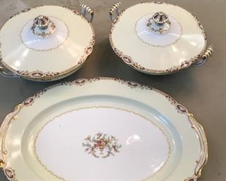 Antique platter with two covered serving bowls.