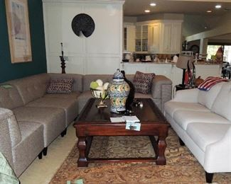 Large sectional sofa - made of individual pieces. Large wood coffee table.  Medallion  art.  Ceramic urns and ostrich eggs