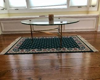 Mid century modern round glass top table  with heavy brass base, small rug