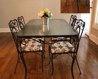Wrought iron glass top table with four matching chairs