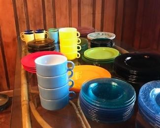 Large amount of colored glass dishes in various sizes.