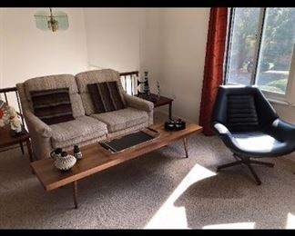 "Extra-Long Unmarked Coffee Table, Sleeper Sofa, ""Control Room"" Swivel Chair"