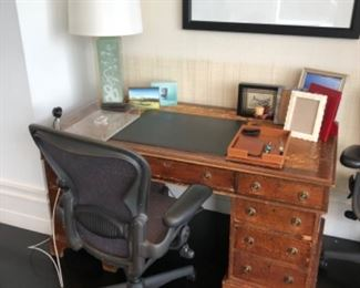 "Antique leather top desk shown with one of two matching desk chairs by Herman Miller, porcelain based lamp and one of two signed prints by  Strasenburgh ""Blue Copper with Dots III"""