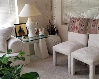 Modern glass side tables and parsons chairs. All white southwest lamps.