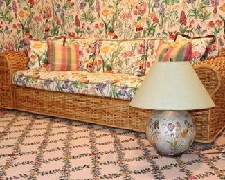 Long Wicker Sofa with Floral Cushions and Lamp