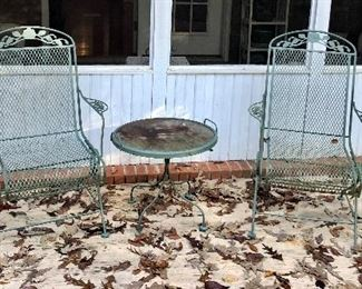 Two straight back metal chairs, round table