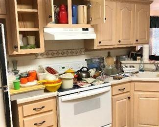 Kitchen full: Tupperware, cheese boards, vintage pot holders, knives, tea kettle, silverware...
