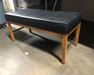 Bench with black leather upholstered cushion.