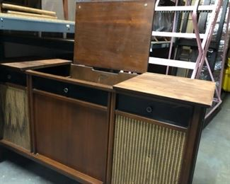 Vintage record player table with vinyl record storage and speaker cabinets.