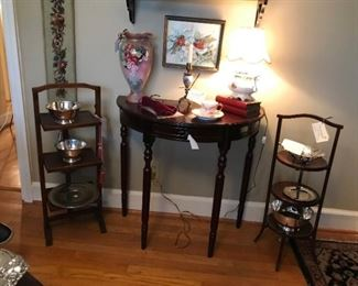 Demi lune table flanked on each side by antique muffin stands