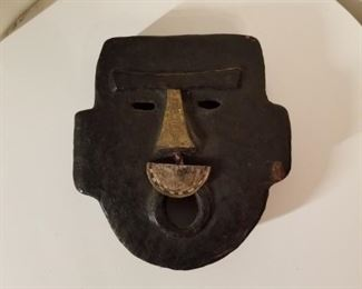 Maker's name on back, 1/2 circle hangs from nose. S. American mask