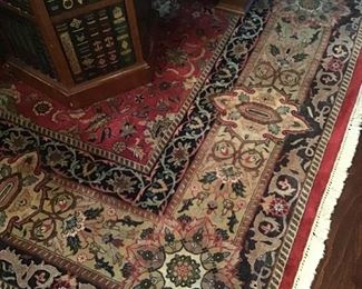 Detail of one of the many Oriental rugs, faux book table
