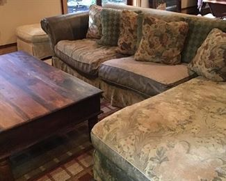 Leather and floral sectional, geometric rug, wood coffee table