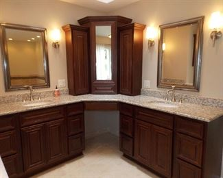 Double vanity with makeup area  mirrors  top of counter cabinets  light fixtures sconces faucets