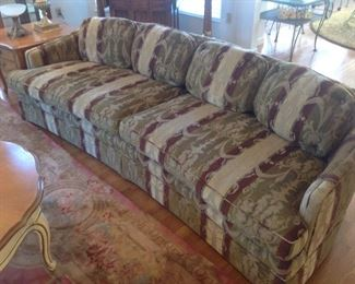 Living Room:  The classic slightly curved sofa has beautiful golden brown, taupe, burgundy colors with a subtle blue stripe.  There are two loose seat cushions and four detached back cushions.  It is 8 feet long and was upholstered by MOEHSNER UPHOLSTERY.