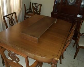 Beautiful dining table with 8 chairs and one leaf.  Also, have the padded table covers.