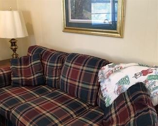 Sherrill plaid couch w/ 2 throw pillows, brass lamp & end table. Woven Christmas throw lays over one end of the couch. Elaine Bradley gold framed print hangs above couch.