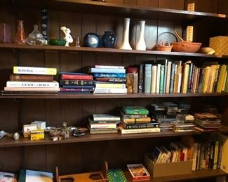 Bookcase filled with vases, books, cassette tapes, 2 brass picture easels, matches & other household ornaments.
