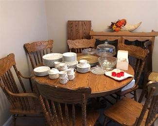 Noritake American Flowers dinnerware set, glass cake stand w/ lid, gold charger plates, crystal bowl on a silver stand, cloth napkins w/ rings, & cornucopia placed on an oak dining room table w/ extra extension leaf & six spindle back chairs. Behind the table is an oak hutch.