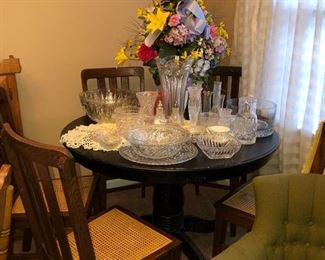 Black pedestal table w/ 5 antique wooden cane bottom chairs. On top of the table is an assortment of various types of crystal & glassware. Large silk flower arrangement in the middle of the table. Crocheted doily & yellow table runners. Green upholstered chair in lower right corner of picture.