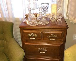 Bedside table with 3 drawers. Tall crystal dish w/ lid, candle sticks & flower shaped candle holder, glassware & pair of silver candle sticks.