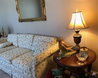 Light colored floral couch w/ 2 throw pillows, decorative antique gold mirror, 2 matching oval end tables, small lamp w/ shade, 2 matching bird figurines, small crystal bowl & antique wooden press.
