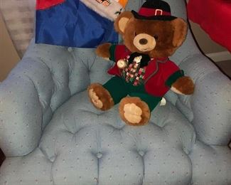 Two of 2 upholstered blue print chairs w/ a Christmas bear, outdoor flag, women's sweater & UT Vols Santa hat on it.