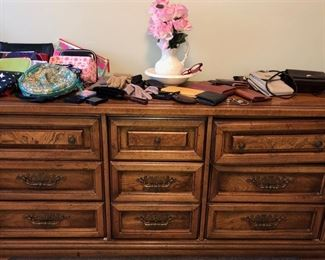 Dresser w/ women's cosmetic bags, small purses, billfolds, gloves and flower pitcher/bowl set. Dresser is part of a queen bedroom suite.
