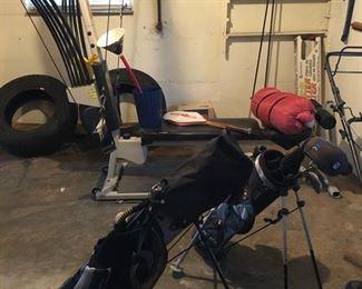 Bow flex exercise system, 2 Jr. golf club sets, tennis racket, sleeping bag, & 2 car tires.