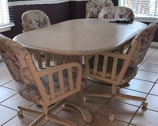 Kitchen table with six captains chairs on wheels