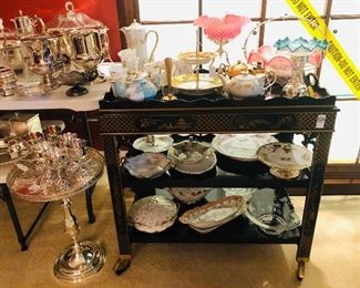 Tea Cart covered in beautiful china and glass pieces beside additional silver pieces