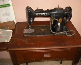 Vintage Singer sewing machine in cabinet with instruction manual and accessories