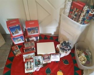 Display of Collectible Christmas Village Parts, Cottages and Lighthouse. Large tall plastic box filled with Christmas wrapping paper and tissues.  Bows and more. Lovely Round Christmas Tree Skirt with bulbs.