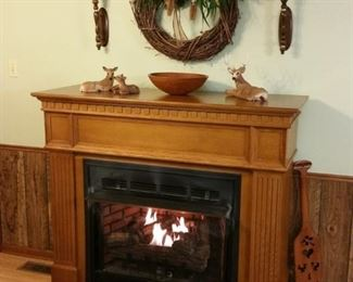 Large free standing fireplace has beautiful oak mantel and natural gas logs that are thermostat controlled.