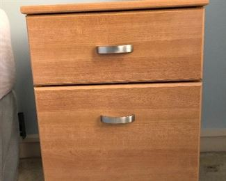 One of two small filing cabinets doubling as bedside tables