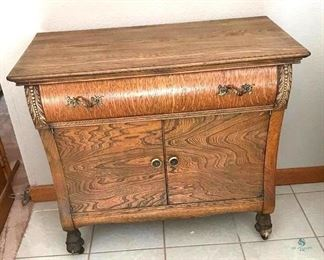 "Antique Wood Sideboard on Casters	 Appears to be Oak, One drawer with Two Doors; Note the detail in the curvature of the wood doors and drawer; 34""w x 18""d x 31""h"