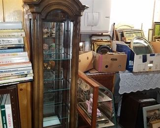 Narrow lighted curio (center) plus end view of curved glass low showcase, and picture frames in background...
