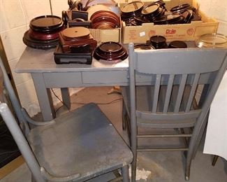 Work table, 2 chairs, and boxes of wood and black glass display stands.  Most in right box are black glass
