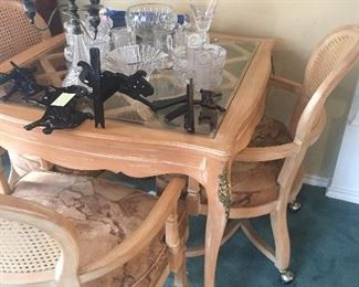 Lovely glass top game table with wood supports and four matching chairs