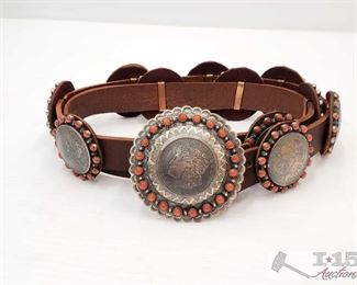 1098: Native American Sterling Silver Coral Concho Belt w/ Morgan Silver Dollar Conchos Signed by Artist This Rare Native American Concho belt.  Has 12 Conchos not including the belt Buckle. The Belt is made out of Sterling Silver and Authentic Morgan Silver Dollars a 100 years old. The conchos are accented with blood red coral. This is a one of a kind Belt.  The leather belt Strap measures  46in. Can Be adjusted to fit any size.  Low Estimate: 2000.00 High Estimate: 3000.00