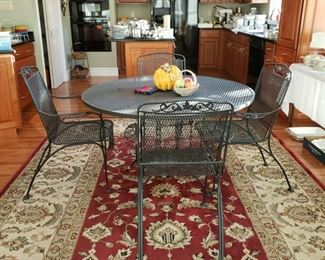 Machine made Oriental style rug and Woodard patio table and four chairs