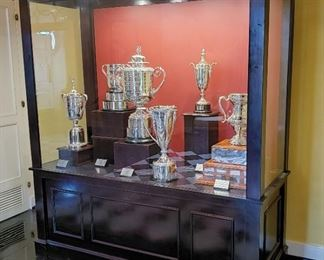 In the Main Lobby is the custom made glass and wood trophy case, appr. 96 inches wide by 33 1/2 inches deep by 73 inches tall