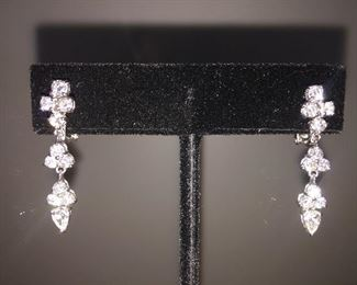 "1.96 CARAT DIAMONDS AND 18K WHITE GOLD SWING DROP EARRINGS: LOTS OF FIRE AND SPARKLE. One pair stamped & tested 18KT white gold lady's hand assembled diamond swing drop earrings. Prong set, omega clip backs with posts and a bright polish finish Identified with markings of ""18kt/750"".   Condition: Excellent. Light scratches on metal.  Signed Appraisal Report included. Total weight of diamonds: 1.96 ct. Total weight of diamond drop earrings: 5.60 grams Contains: Two prong set pear shaped cut diamonds (depth est.) exact total weight 2 stones = 0.41 ct. Clarity SI1 Color G Cut Excellent. Twenty prong set round brilliant cut diamonds exact total weight 20 stones = 1.55 ct. Clarity SI-1. Color F-G. Cut: Excellent. Length of earring: Approximately One and one-quarter inch.  Width of earring: Approximately 1/4 inch at its widest. Gift Box Included. Price: $3,700."