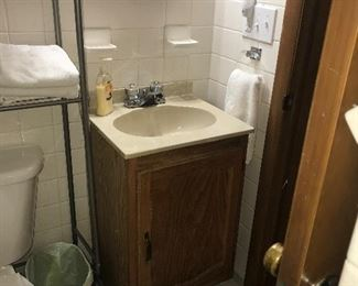 Small bathroom vanity, mirror, door, commode, rack, face plates.  Everything, including the walls, is for sale!