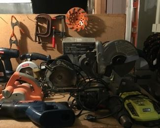 Black and Decker Circular Saw, Craftsman Auto Scroller Saw, Mikita 10in Miter Saw, Black and Decker Jig Saw, Ryobi 18 v One and Dual Chemistry Intelliport Charger. Background: Clamps and Diamond Saw Cutting Blade.