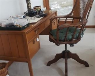 Vintage desk and  early 20th century oak and cane clerks/desk chair.