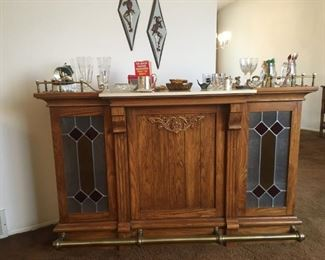 Oak bar with stained glass panels lighted and faux marble counter top, drawer & shelves in back of bar