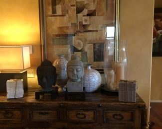 Spanish Colonial revival sideboard,  two of many Buddha heads, Portuguese pottery, exciting lighting and prints. Don't forget to set the mood with candles and oversize hurricane lamps.