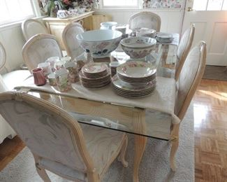 glass top whitewashed wood table with six fabric covered chairs